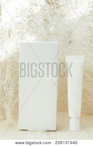 Front View. Package Box And Cream Placed On Wood Floor Have Abstract Material Are Background. Image