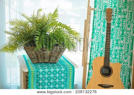 classic guitar placed beside wooden table with wooden basket has green plant placed on top. green cloth and cement wall are background. image for music place travel instrument nature concept