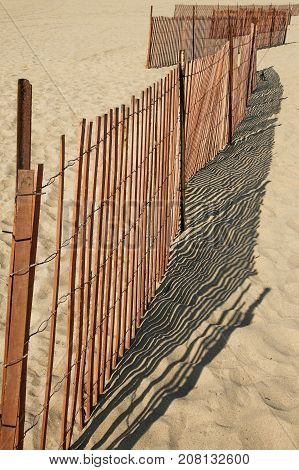 Wooden and metal railing casting its shadow on the sand along the beach.