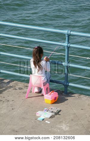 An unidentified girl fishing or playing with her small fishing rod on a pier off the Pacific Ocean. In the image we also see some additions of the sport fishing.