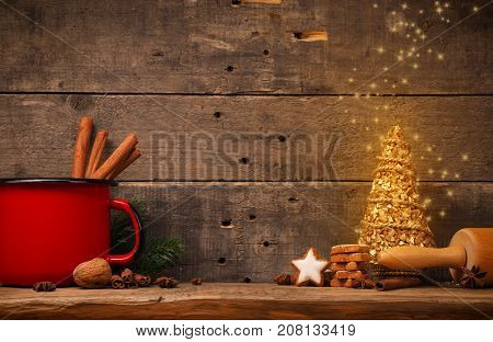 Christmas background with baked cinnamon star cookies and red pot on a wooden board Christmas tree with glittering stars