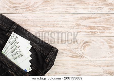 one hundred euro banknotes in a jeans pocket on white wooden background with copy space for your text. Top view.