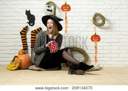 Halloween girl winking with gift box and bag. Woman in witch hat sitting on floor. Happy holiday celebration. Surprise and present concept. Pumpkins stockings wreaths cat mummy decorations on wall