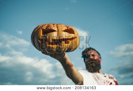 Halloween Pumpkin With Red Blood In Male Hand On Foreground