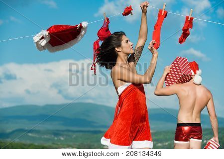Xmas red costume on rope with pin. Laundry and dry cleaning. New year guy with muscular body on blue sky. Couple in love of man and girl hanging clothes for drying. Christmas man and woman family.
