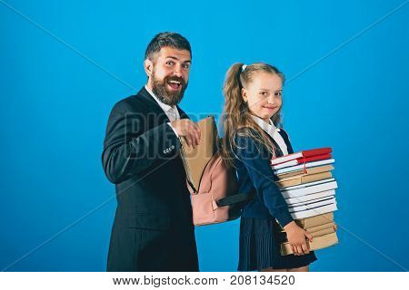 Home schooling and back to school concept. Kid holds heavy books and tutor puts book into backpack. Teacher and schoolgirl with happy faces on blue background. Bearded man and girl in school uniform