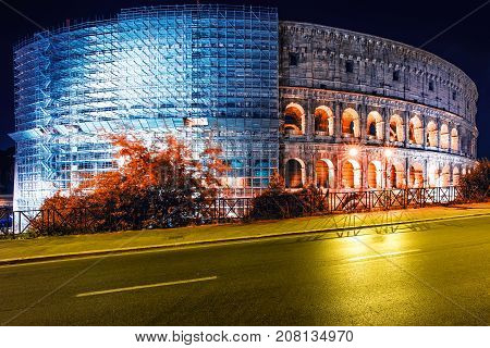 Colosseum with scaffolding under restoration at night Rome Italy. Roman amphitheatre with light illumination on dark sky. Renovation repairing retouching concept. Landmarks and architecture.