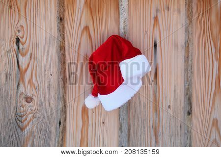 Santa claus hat on fence. Red santa cap on wooden background. Palisade planks with timber texture. Christmas and new year. Holidays celebration concept.