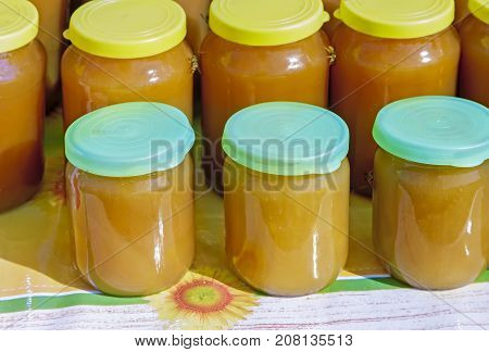 Fresh honey of different sorts in glass jars with lids held for sale at the fair.