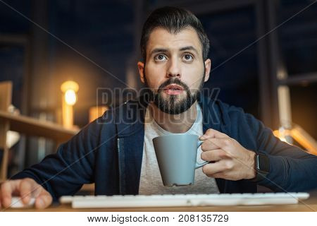 At workplace. Concentrated brunette opening mouth and holding cup in left hand while looking at screen of his computer