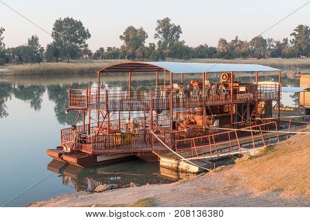 UPINGTON SOUTH AFRICA - JULY 7 2017: Sunrise at Sakkie se Arkie a river boat at a holiday resort with the same name next to the Orange River at Upington