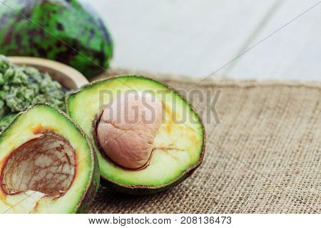 cut of avocado and green on sackcloth.