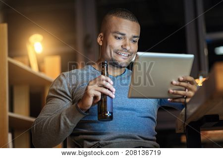 Good news. Handsome man holding bottle of beer and looking at screen of tablet while being in the office