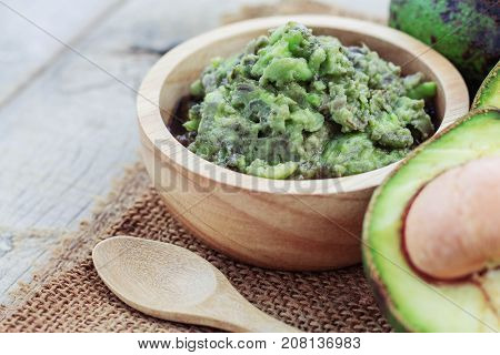 Grated avocado in bowl and spoon on sackcloth.