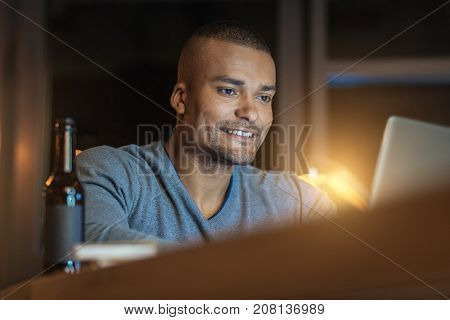 Have an idea. Enigmatical office worker expressing positivity and looking at computer while sitting in semi position