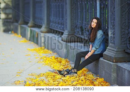 Young long-haired brunette sitting on a concrete curb around the cast-iron fence under the feet of yellow autumn maple leaves side view.