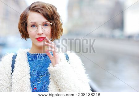 Portrait of young beautiful pensive woman in glasses on a city street in the blurry background. Close-up.