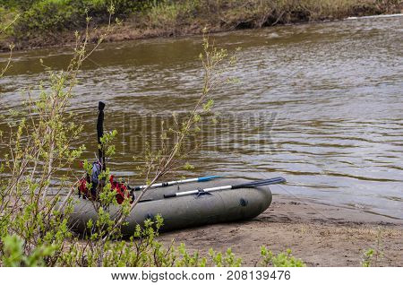 The river bank of the small small river with a rapid current. The inflatable boat with oars ashore