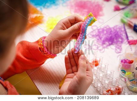 Colored rubber bands for weaving accessories in the hands of a girl on a wooden background