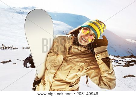 Happy girl snowboarder with snowboard smiling on ski slope backdrop. Skiing concept