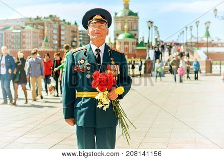 Yoshkar-Ola, Russia - May 9, 2015 Unknown veteran of World War II, standing with flowers on the street of Yoshkar-Ola, Russia