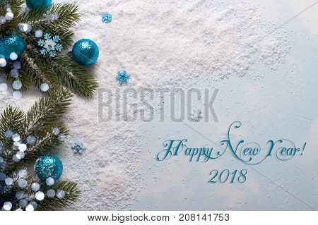 Blue New Year 2018 decorations with festive ornaments on snow, flat lay with cope space