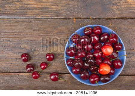 Various summer Fresh Cherry in a bowl on rustic wooden table. Antioxidants, detox diet, organic fruits.