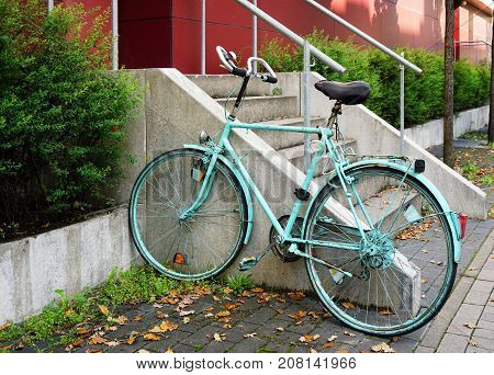 painted bicycle locked to railing in front of student residence in Germany