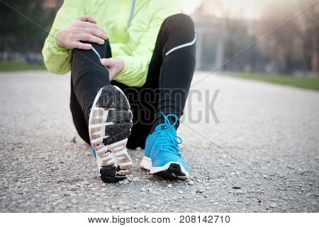 Runner With Injured Ankle While Training In The City Park In Col