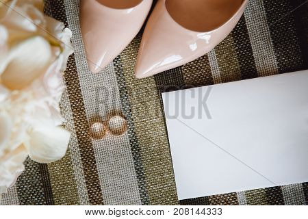 Wedding accessories: bride shoes, earrings, bouquet, invitation, rings. View top
