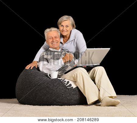 Senior couple resting with laptop on black background