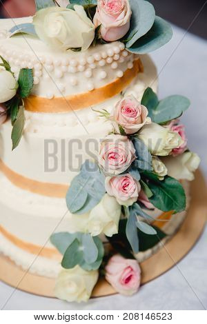 wedding cake with fresh flowers roses. three tiers