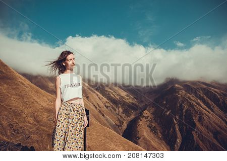Romantic free dreamy woman with closed eyes, hair wind enjoy harmony with nature. Peace of mind. Happy dreamer, inspiration background. Mountain landscape. T-shirt with word Travel. Time to travel