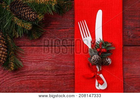 Christmas table place setting with red napkin, white fork and knife, decorated sprig of mistletoe and christmas pine branches. Christmas holidays background.