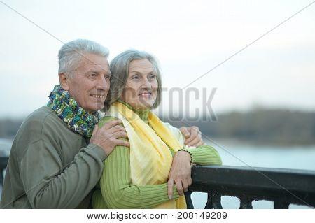 Happy senior couple near water at autumn park