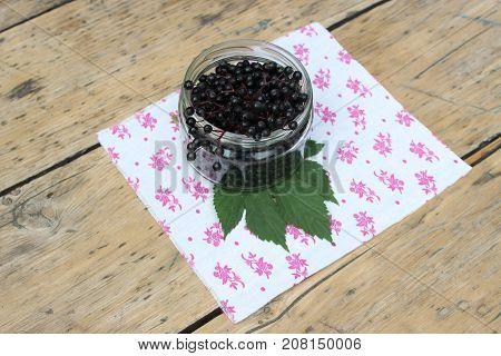 Ripe elderberry fruits in a glass jar