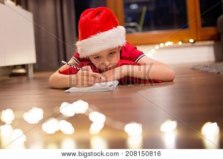 Little Boy Child In Santa Claus Cap Writing A Letter To Santa.