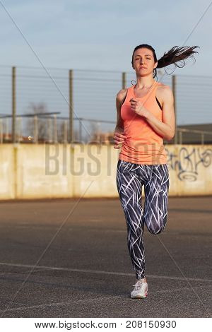 young brunette woman running on urban way