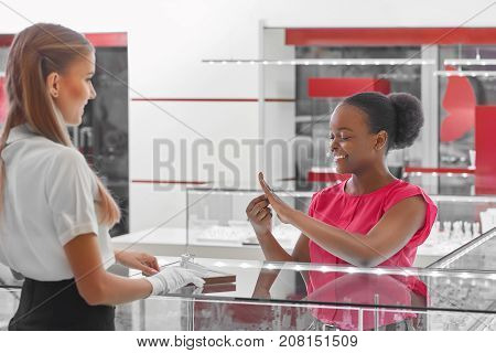 Shot of a happy African young woman smiling joyfully trying on rings at the jewelry store.