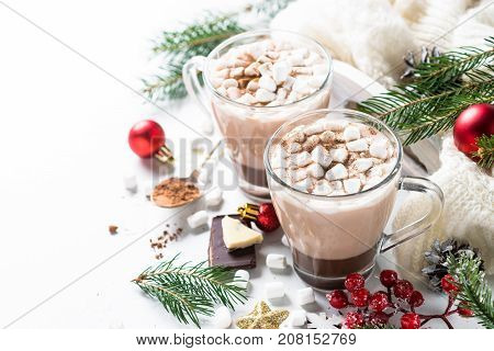 Winter hot drink. Christmas hot chocolate or cocoa with marshmallow on white with christmas decorations. View with copy space.