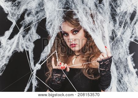 Portrait of Beauty Sexy Witch girl caught in a spider web. Fashion Art design. Beautiful Gothic model girl with Halloween make up and costume. Close-up shot