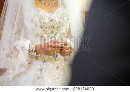 Hands of bride preparing for holy communion at wedding holy matrimony ceremony in church