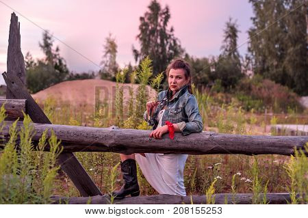 a young cowgirl at sunset near a rustic wooden fence