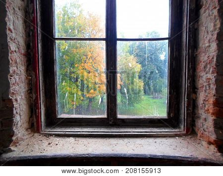 View of the autumn park through an old dirty window in abandoned palace in Belarus (Zheludok, Grodno region), built in the early twentieth century, example of Art Nouveau style