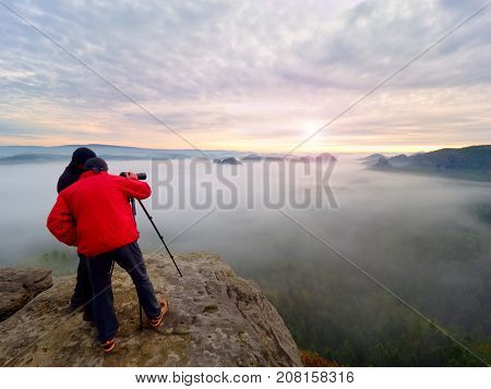 Photographying In Wild Nature. Nature Photographer With Big Camera On Tripod Stay On Summit Rock. Li