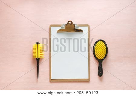 Flat lay of hair comb crest brushes with handle for all types, pocket mirror and folder tablet, isolated on pink copy space background. Minimalistic feminine flat lay for bloggers, designers, sites.