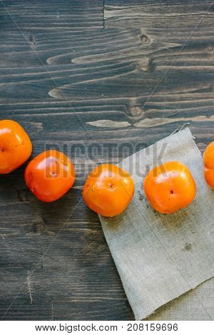 Top view of persimmon snake on brown wooden table.