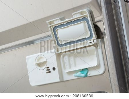 Open Dispenser In A Dishwasher With Clean Plates, Cups And Dishes