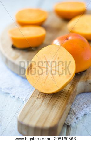 Half of persimmon fruit on wooden board