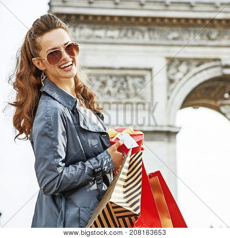 Stylish Christmas in Paris. Portrait of happy young woman  with shopping bags and Christmas present near Arc de Triomphe in Paris France